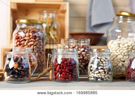 Assortment of haricot beans in glass jars on kitchen table