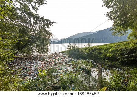 Big lake in mountains with lot of garbage trash cans and bottles in water. Ecology catastrophe environmental pollution concept