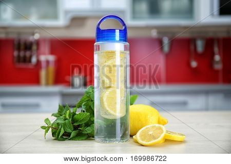 Bottle with lemon-infused water and mint on kitchen table