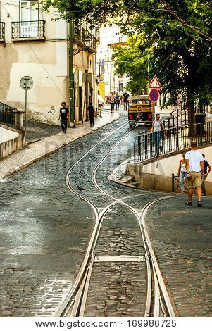 Lisbon, Portugal - Septmember 19, 2016: People walking along the road and the tram tracks, on the way to neighbourhood Graca