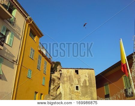 Nice old house colorful houses roofs paragliding in the blue sky. Cote d'Azur French Riviera Provence France