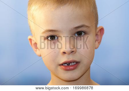 Close-up Of Boy Smiling With Missing Front Milk Tooth Over Light Background. A Young Boy Showing Off