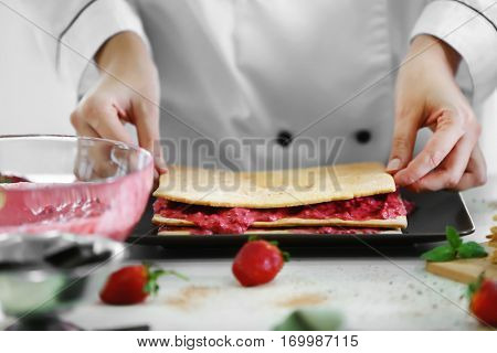 Cooking concept. Professional confectioner making delicious cake with fruit cream, closeup