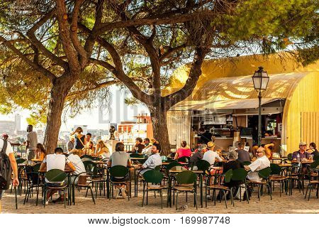 Lisbon, Portugal - Septmember 19, 2016: Viewpoint of neighbourhood Graca busy with tourists enjoying the beautiful scenery in the shade drinking coffee