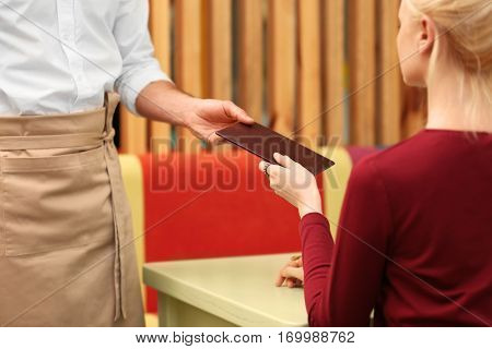 Client getting bill from waiter at restaurant, closeup