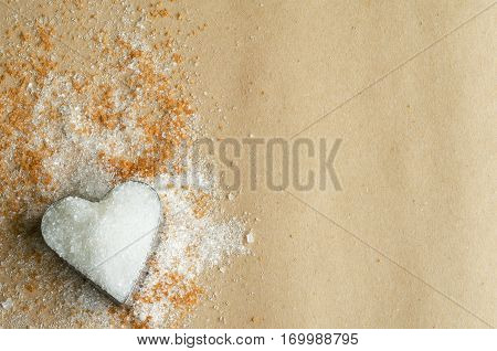 Heart shape filled with white sugar on paper background