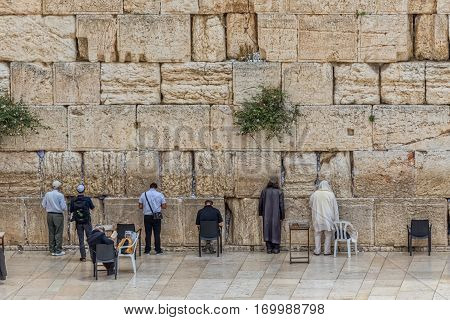 JERUSALEM, ISRAEL - MAY 24, 2016: Prayers making their wishes and prays at the Western Wall, Wailing Wall or Kotel witch is located in the Old City at the foot of the western side of the Temple Mount.
