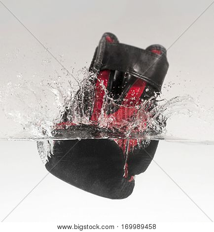 Boxing glove punches through the water and makes a splash.