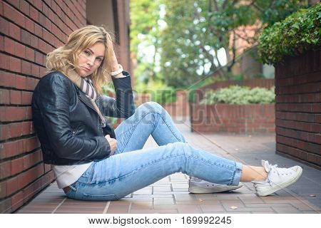 Young attractive serious woman sitting near brick wall, looking with mixed emotions, reflecting on something, disappointed, maybe frustrated.