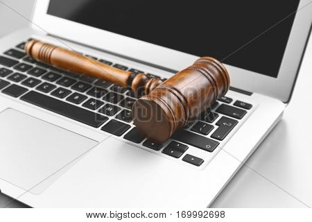 Wooden judge's gavel on laptop keyboard, closeup
