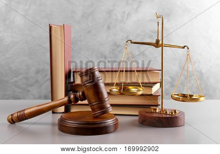 Gavel with books and scales on grey wall background