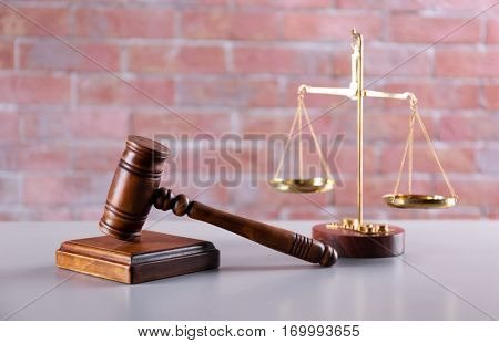 Gavel with sound block and scales on brick wall background