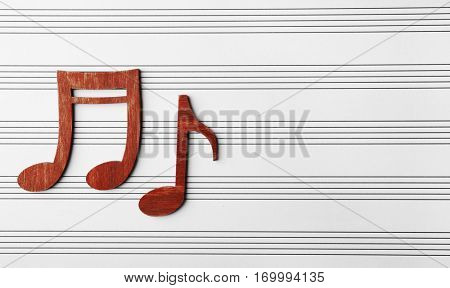 Wooden musical notes on music sheet background
