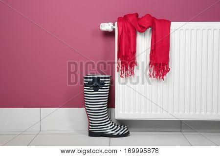 Gumboots and scarf near heating radiator on pink background