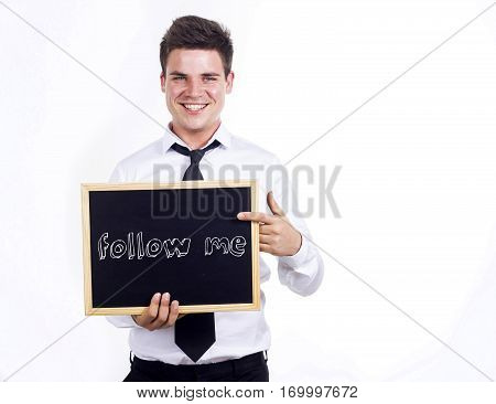 Follow Me - Young Smiling Businessman Holding Chalkboard With Text