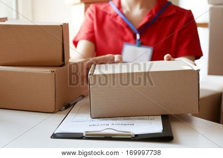 Courier hands giving packaged parcel at table