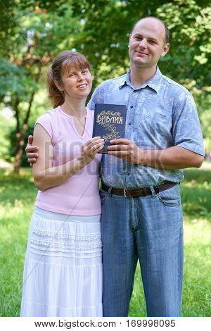 man and woman with a book named Bible in his hand, text on russian language
