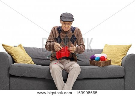 Clueless senior sitting on a sofa and knitting isolated on white background