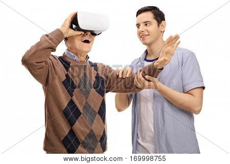 Young man holding a mature man hand while he is using a VR headset isolated on white background