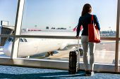 Travel tourist standing with luggage watching sunset at airport window. Unrecognizable woman looking at lounge looking at airplanes while waiting at boarding gate before departure. Travel lifestyle. poster