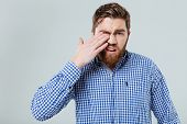 Upset bearded young man standing and rubbing his eye poster