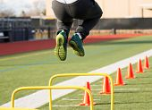 A track and field athlete jumps over yellow hurdles before he funs over orange cones all on a green turf field poster