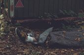 Feet and lower legs wrapped in tarpaulin of murdered person in leafy countryside poster