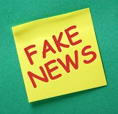 The words Fake News in red text on a yellow sticky note as a reminder to be aware of hoaxes and disinformation for propaganda uses poster