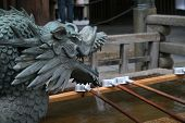 Dragon fountain of Japanese Tsukubai at an old temple - provided at the entrance to holy places for visitors to purify themselves by the ritual washing of hands and rinsing of the mouth poster