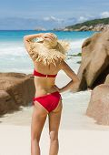 Slender woman in straw hat, red swimsuit, beach in Seychelles poster