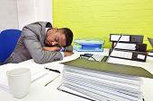 Indian businessman asleep at his desk poster