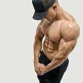 Shirtless male with muscular build strong abs showing. Perfect fit six pack abs shoulders deltoids biceps. Bodybuilder in black cap with muscular physique looking down. Vector clipping mask path poster