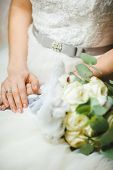 Bride sitting with crossed hands in wedding ring and bridal bouquet near her. White dress with bow on waist. Wedding bunch of fresh flowers, romantic accessory of fiancee. Excellent manicure on nails poster