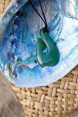 close up of carved maori nephrite jade / greenstone pendant on paua shell with kite bag in background poster