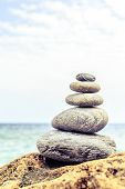 Stones balance and wellness retro spa concept inspiration zen-like and well being tranquil composition. Close-up of white pebbles stack over blue sea poster