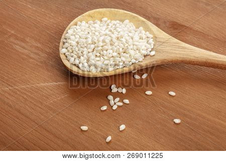 A Closeup Photo Of Spanish Calasparra Rice Used For Paella In A Wooden Spoon On A Rustic Background