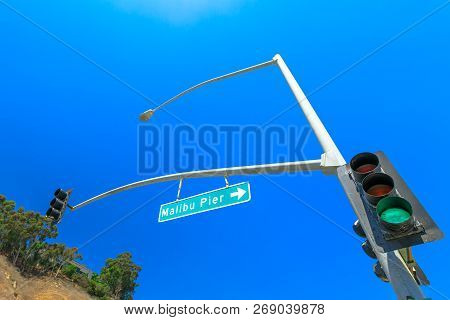 Bottom View Of Green Traffic Light And Malibu Pier Sign In The Sunny Day With Blue Sky. Malibu Pier