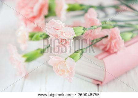 Soft Pink Carnation Flowers And Book On A Blurred Background. Soft Focus