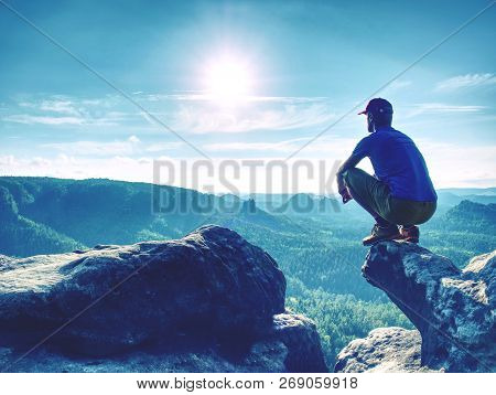 Fearless Man In Sportswear Is Sitting On Cliff Edge And Looking To Far Horizon.