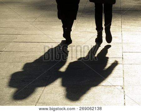 Two Women Shadows On Pavement. Black Silhouettes Of People Walking Down The Street, Dramatic Lightin