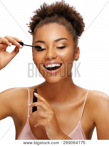 Smiling Girl Applies Black Mascara On Her Eyelashes. Photo Of Young African Girl Finishing Her Makeu