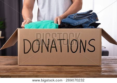 Young Man Donating Clothes In Donation Box Over Wooden Desk