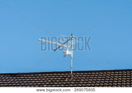 Tv Antenna On The House Roof. Blue Sky Background.