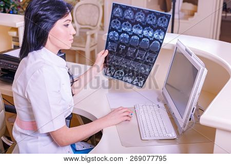 Female Doctor looking at a tomography x-ray picture poster