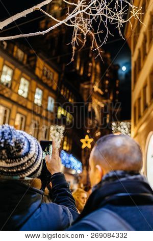 Adult Male Couple Taking Photo On Smartphone Of Notre-dame Cathedral And Maison Kammerzell Decorated