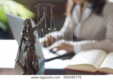 Lawyer Office. Statue Of Justice With Scales And Lawyer Working On A Laptop. Legal Law, Advice And J