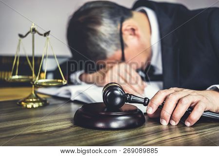 Judge Gavel With Lawyers, Gavel On Wooden Table And Counselor Or Male Lawyer Is Tired And Migraine H