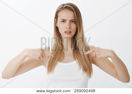 Intense Girl With Serious Face Pointing At Herself As Asking Question, Concerned And Unsure Frowning