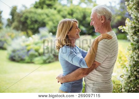 Smiling senior couple embracing outdoors
