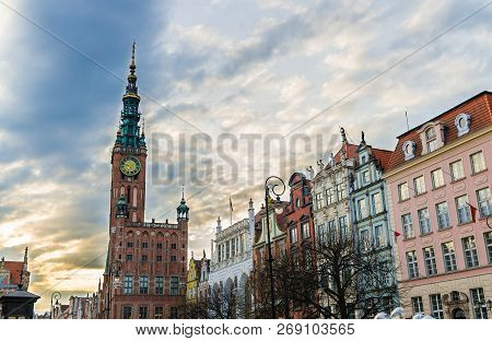 City Hall With Spire, Clock Tower, Facade Of Beautiful Typical Colorful Houses Buildings At Dluga Lo